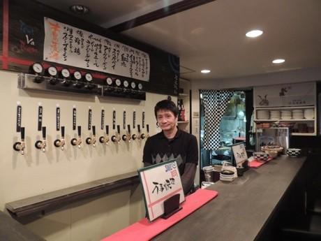 「KRAFT WORK DINNING 万事快調」店内。カウンター内は店主の岩崎さん。壁にはクラフトビールが出る「タップ」10個が取り付けられている