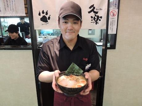 「白味噌らーめん」を持つ店長の嶋崎さん