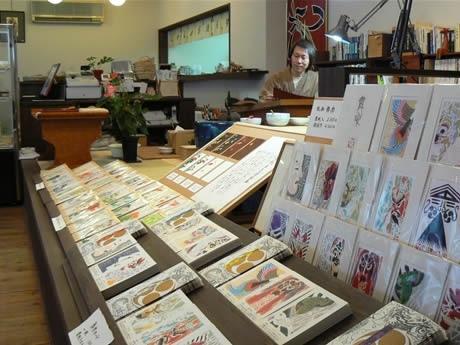 木版画家の古河泰九さんの工房・ギャラリー「土筆舎」作品のカードが並ぶ。この奥にお豆腐カフェ「まめく」があり、豆乳やパック入りの豆腐も購入できる。