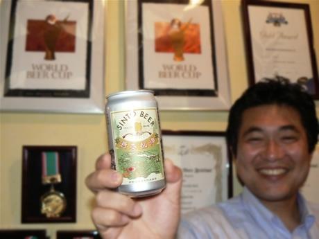 ジャパンビアカップ3年連続金賞受賞した「神都麥酒」を手にする鈴木社長。壁にはこれまでに受賞した表彰状の数々。