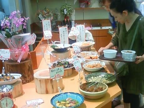 毎日店頭に並ぶ料理は30品目以上。グラム単位で購入できる。写真は料理の多さに迷う客。