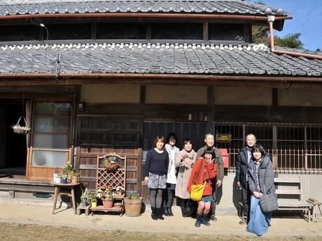映画「きいろいゾウ」ロケ地巡礼-松阪市「ムコとツマの家」・南伊勢町「ソテツ」など。写真は「ムコとツマの家」の玄関でガイド役の西井会長を囲んで記念撮影するファン