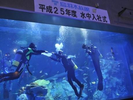 鳥羽水族館で「水中入社式」-黒のスーツの上に空気ボンベ背負って