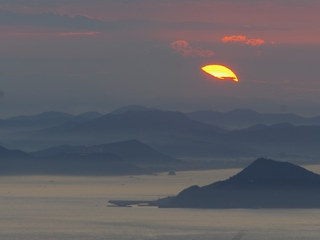 夏至の日に伊勢志摩最高峰・朝熊岳から富士山と太陽重なる。よく見ると宝永山のシルエットも確認できる(撮影2015年6月22日4時46分=北井誠也)