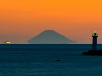 「富士山が宙に浮きだした」冬の到来 志摩の海岸から写真家の泊正徳さんが撮影
