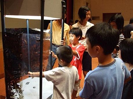 竜巻を発生させる機械を使った実験では、子どもたちが竜巻に触れようと手を伸ばす