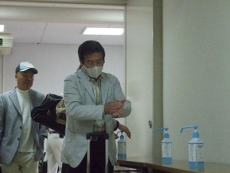 石垣空港の到着ロビーに設置された消毒液で消毒を行う乗客