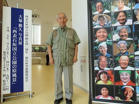 写真家の大塚勝久さん。会場入口には島の人々の笑顔が並ぶタペストリーが設置