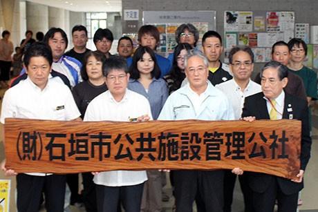 取り外した看板を手に写真に収まる中山義隆石垣市長(左前)ほか職員ら