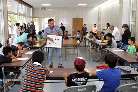 石垣に生息するクワガタムシを説明する世界の昆虫館館長の山田守さん