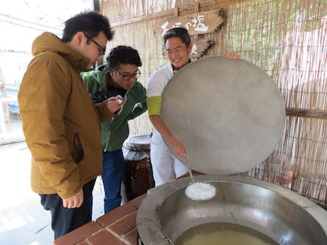 石垣の塩工場で塩の結晶を手に取るIDEA N DESIGNさん(左)