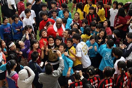 ボブ(中央赤色のシャツ)さんは一人一人と握手やサイン、写真撮影に応じ、生徒は輪になるようにボブさんを囲んだ