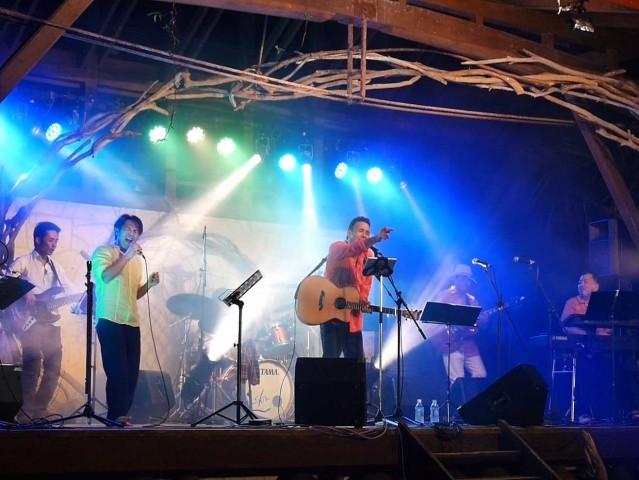 「オキナワンハート」を熱唱する池田真作さん(舞台中央)とコーラスで参加した伊良皆誠さん(前左)