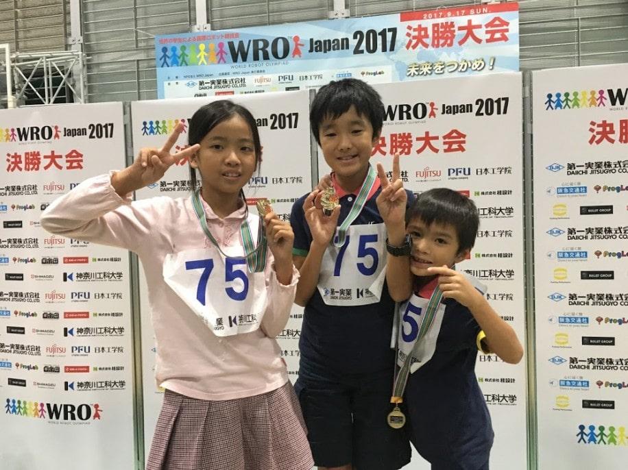 表彰台で笑顔の3人