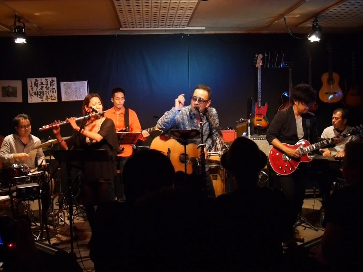 豪華なバンド編成で、オリジナル曲を熱唱する池田真作さん(舞台中央)