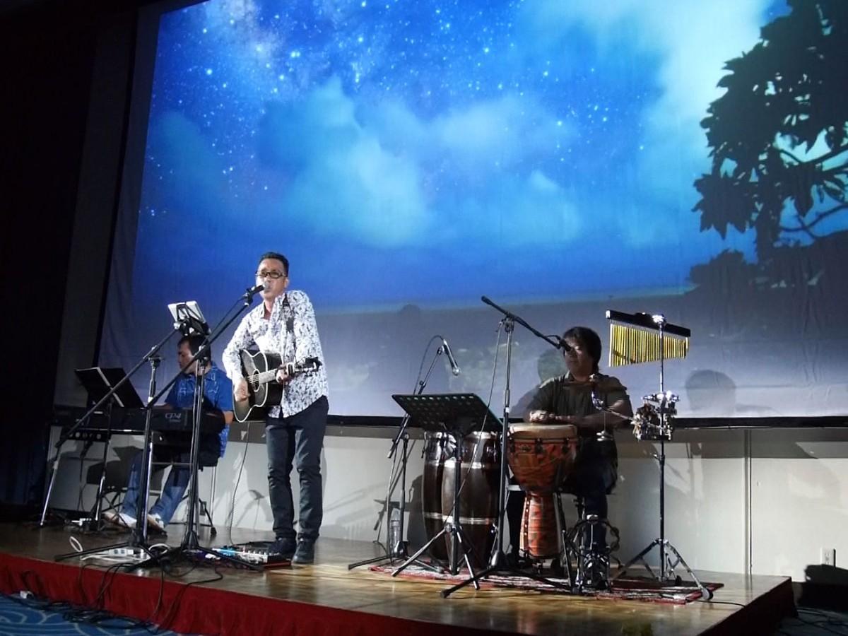星空の映像を背景に歌う池田真作さん(舞台中央)