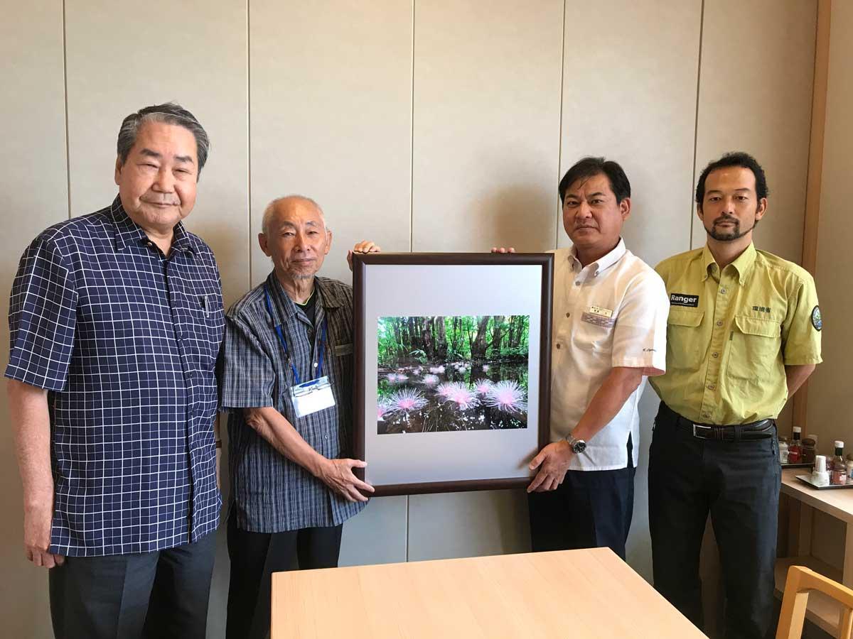 ホテルミヤヒラの親盛一功社長(右から2人目)に写真額を手渡す大塚勝久さん(左から2人目)