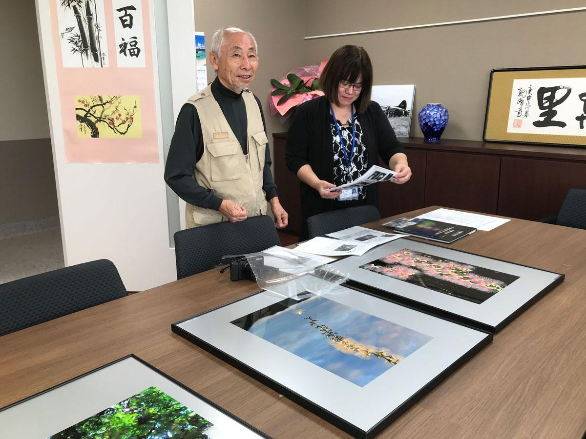 寄贈した写真を前に話す大塚勝久さん(左)と八重山病院の篠崎裕子院長(右)
