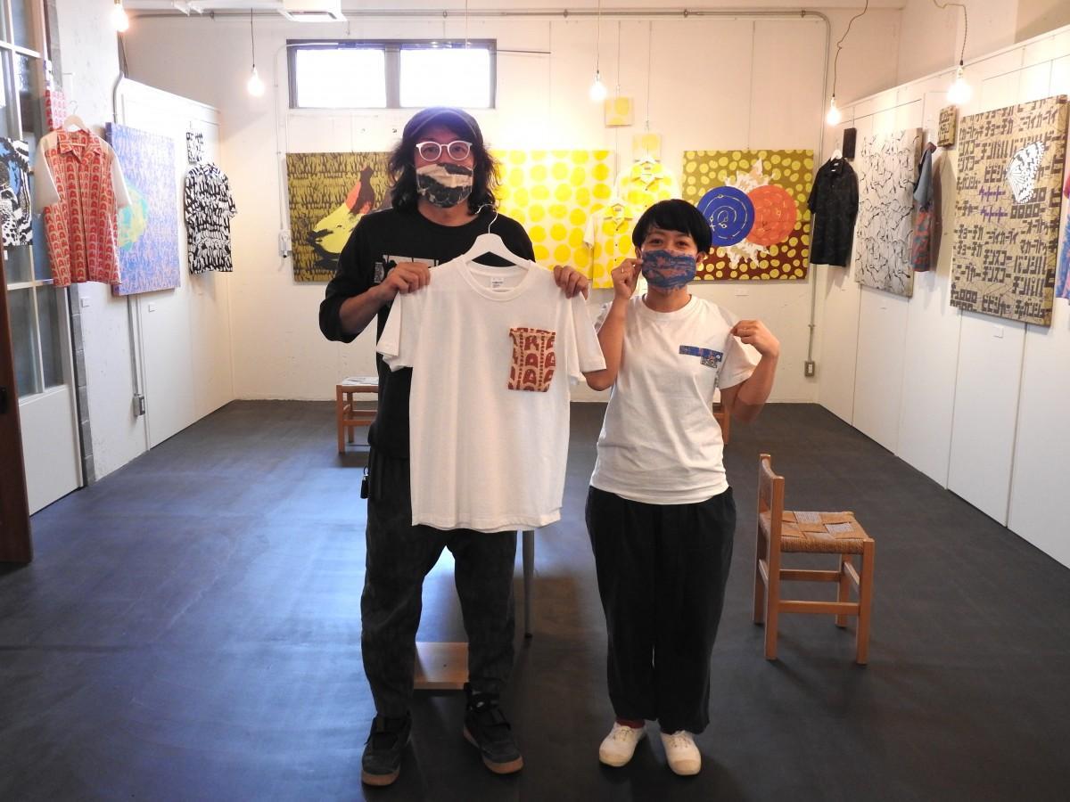 胸ポケットが取り外し式のマスクにもなる新作シャツ「マスポTシャツ」を手にする池城安武さん(左)と小浜まどかさん(右)