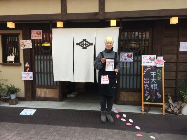 店の前でチラシを見せる坂井善三商店の坂井祐江さん