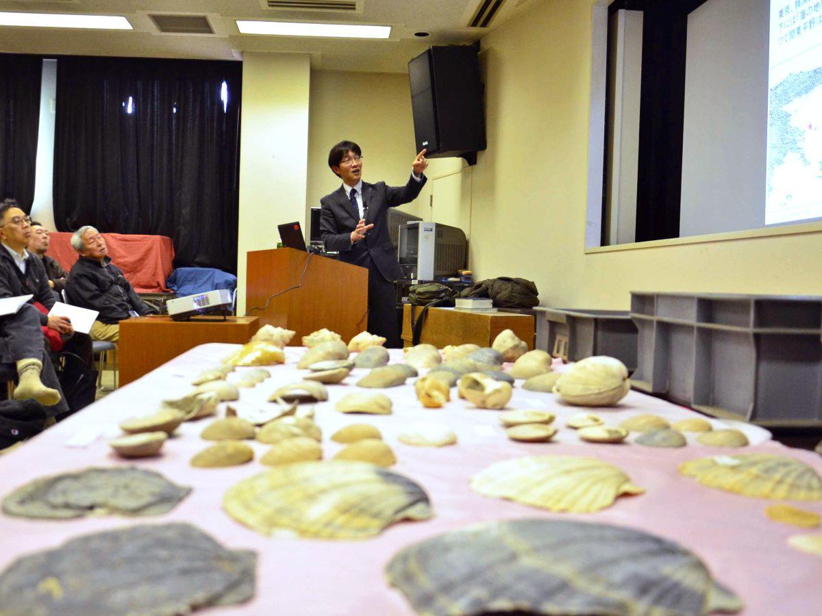 貝化石を前に講演を行う川辺文久さん