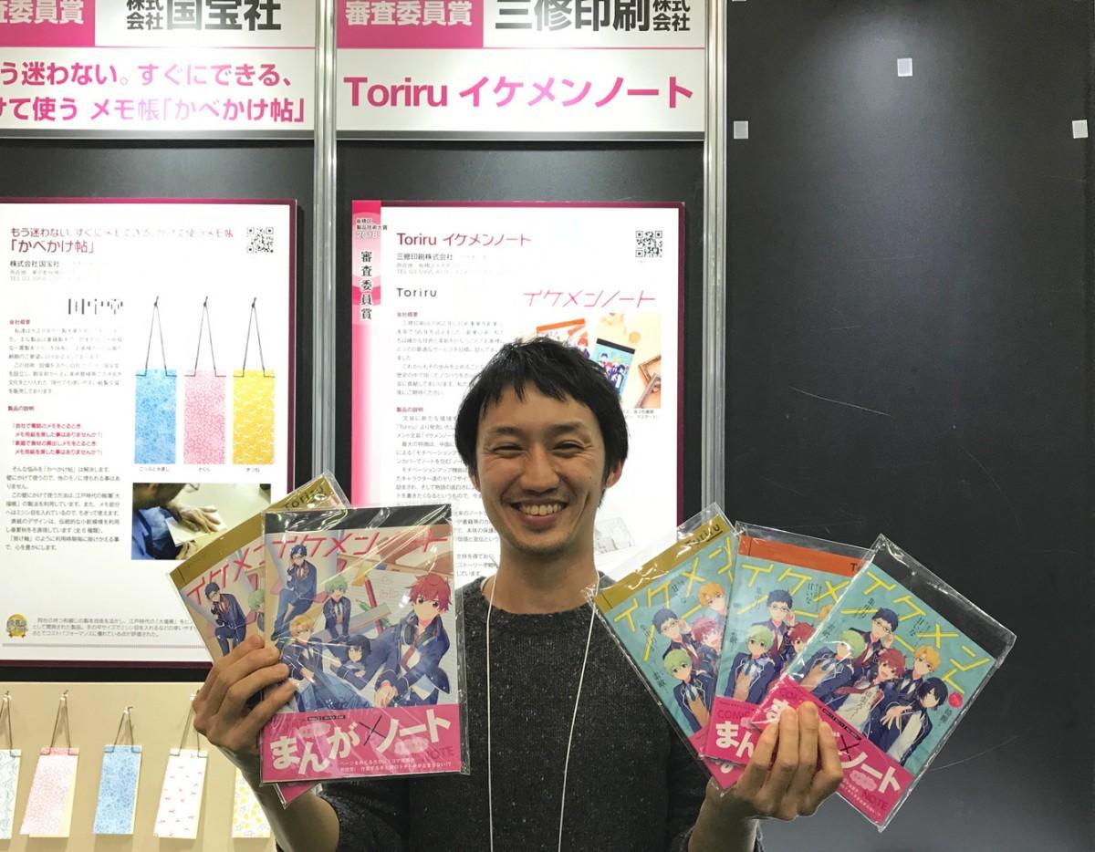 見本市会場でイケメンノートを手にする松浦賢さん