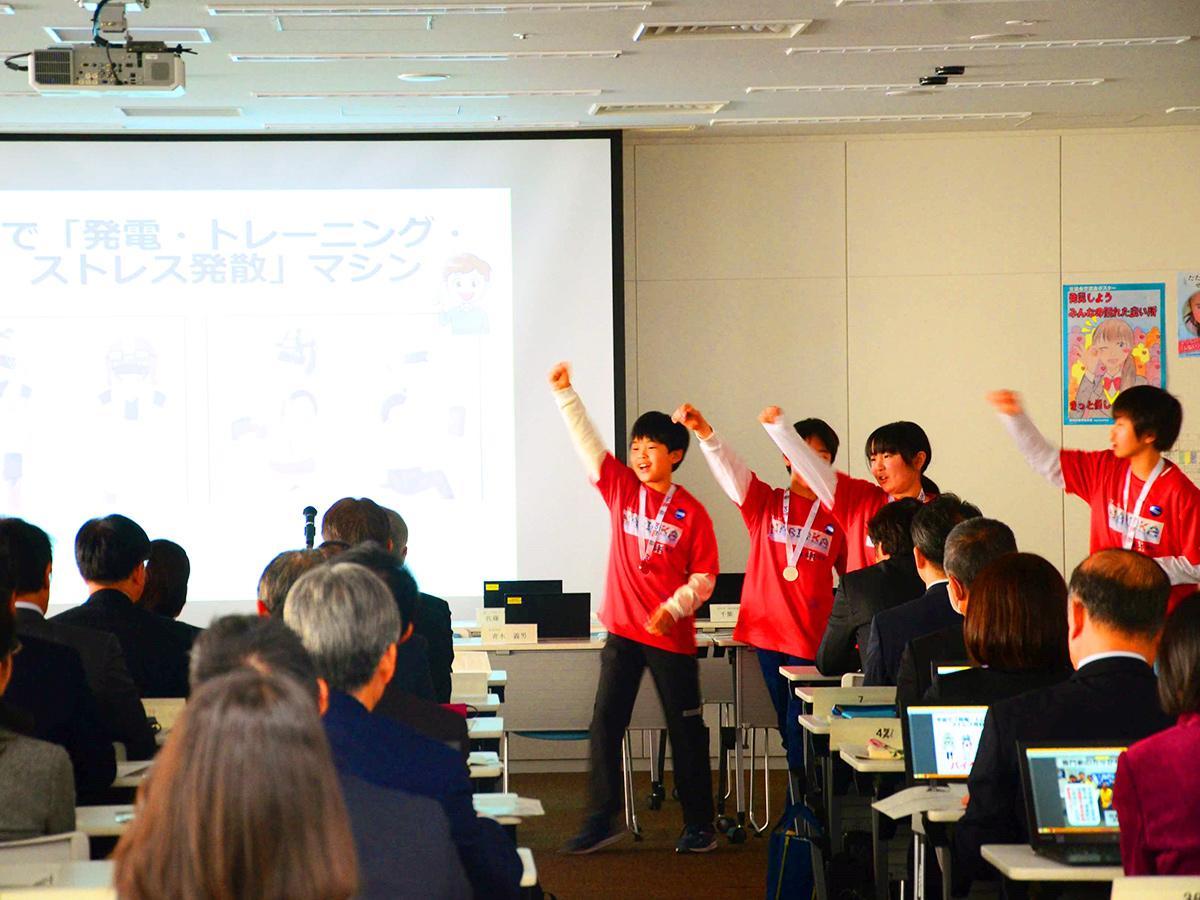 板橋区役所でプレゼンテーションする「TEAM NARIOKA II」の4人