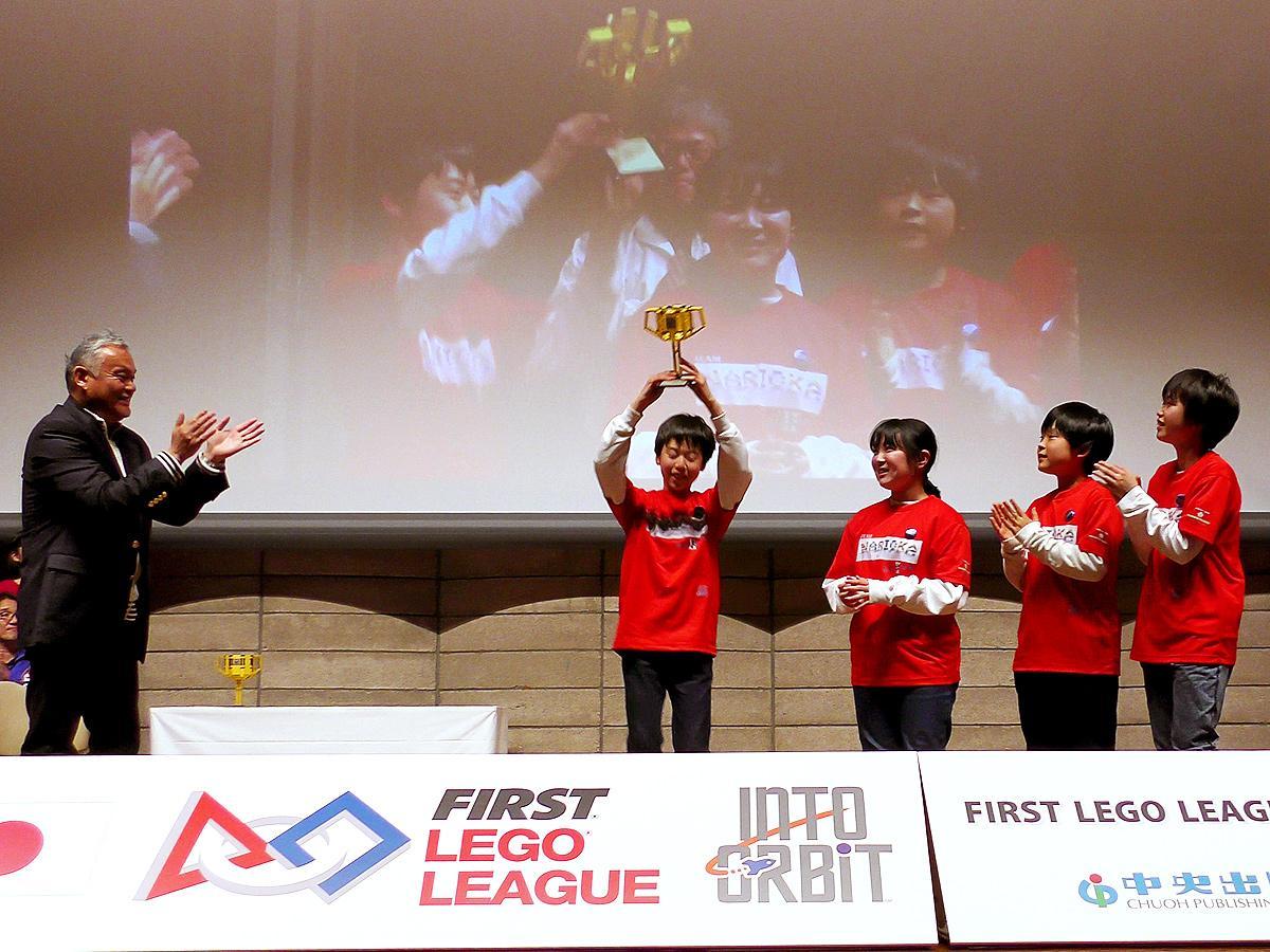 授賞式でトロフィーを掲げる「TEAM NARIOKA II」