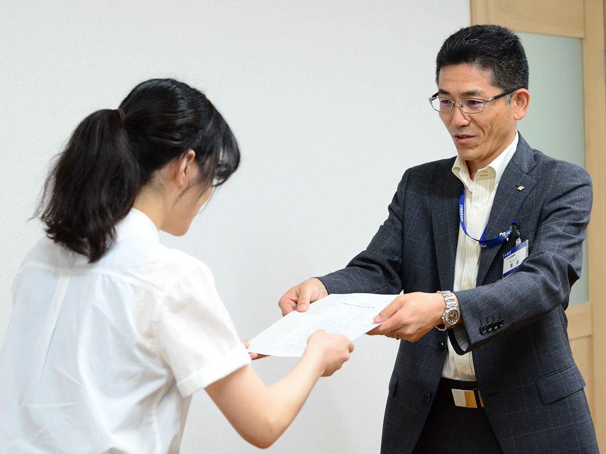 交付式で支援対象者に証書を授与する雨谷周治課長