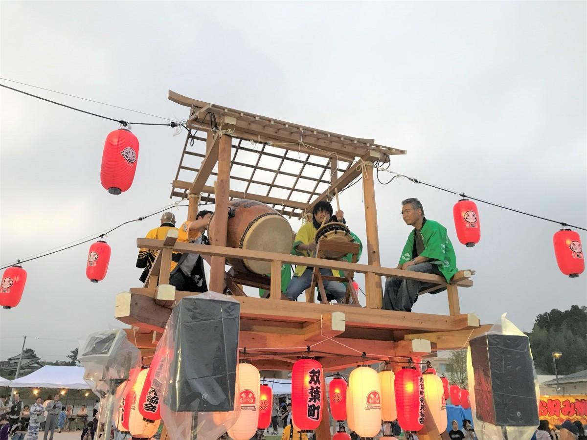櫓で応援演奏する、夢ふたば人の中谷さん(中央)と、指揮する標葉せんだん太鼓保存会の横山さん(右)。