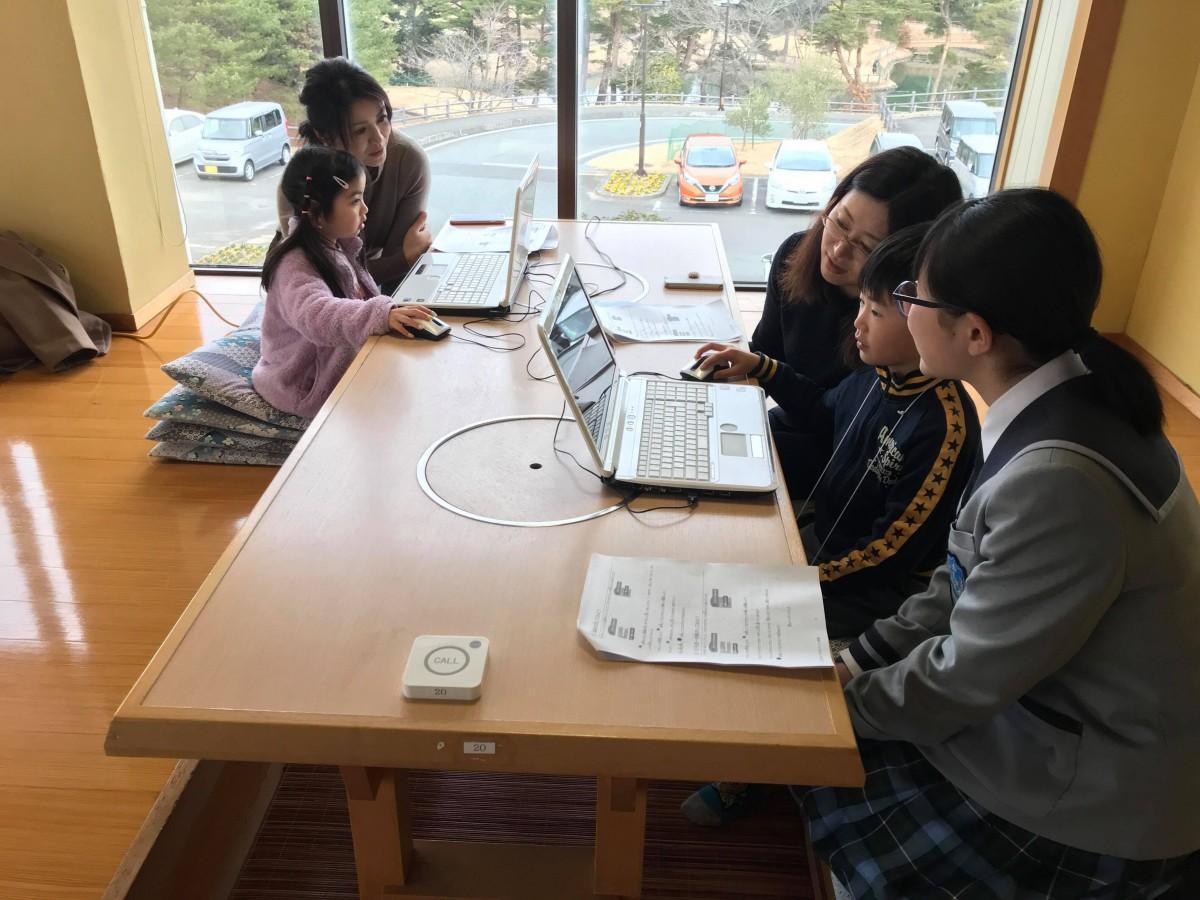 プログラミングを体験する親子とサポートする中学生