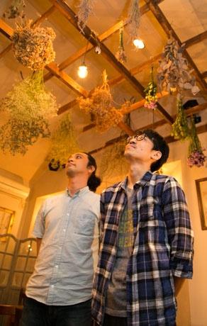 天井に吊るされたドライフラワーを眺める中村さん(右)と、林さん