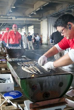 振る舞うサンマを焼く漁港関係者たち