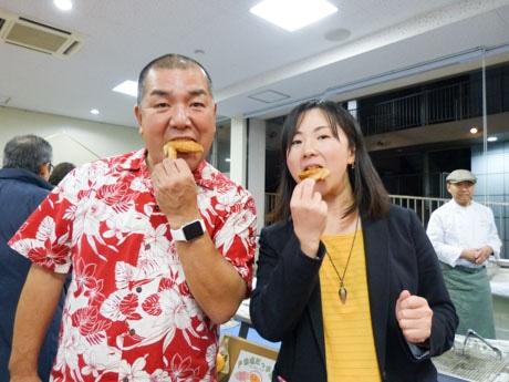 揚げたての空揚げを頬張る鳥居会長(左)と川村事務局長