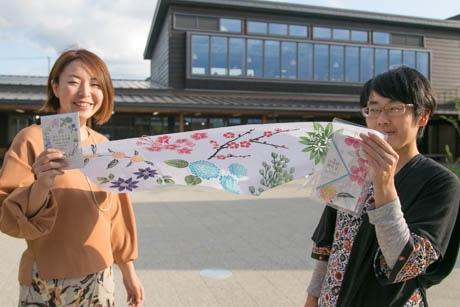 伊豆の花をあしらった手ぬぐいを持つすみさん(左)と津久井さん
