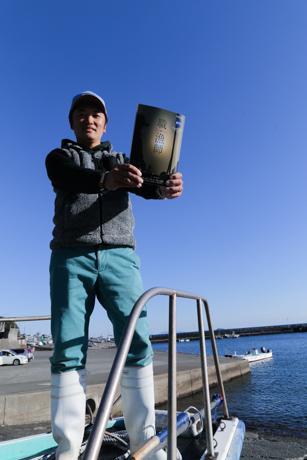 「職・漁師」」を手にする漁師の平山さん