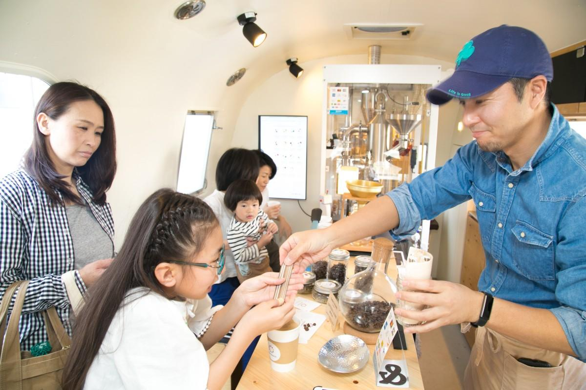 店内でコーヒーの説明をする岡田さん(右)