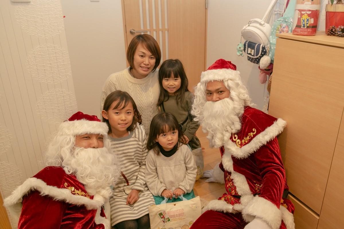 宅配サンタたちと記念撮影する子どもたち