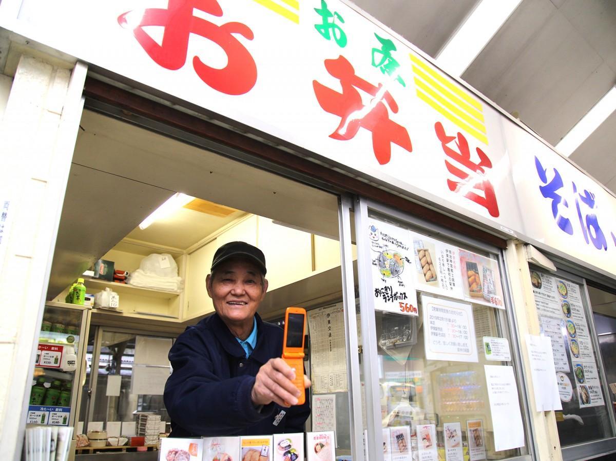 売店から携帯電話を差し出す、勤務歴60年の稲葉さん。