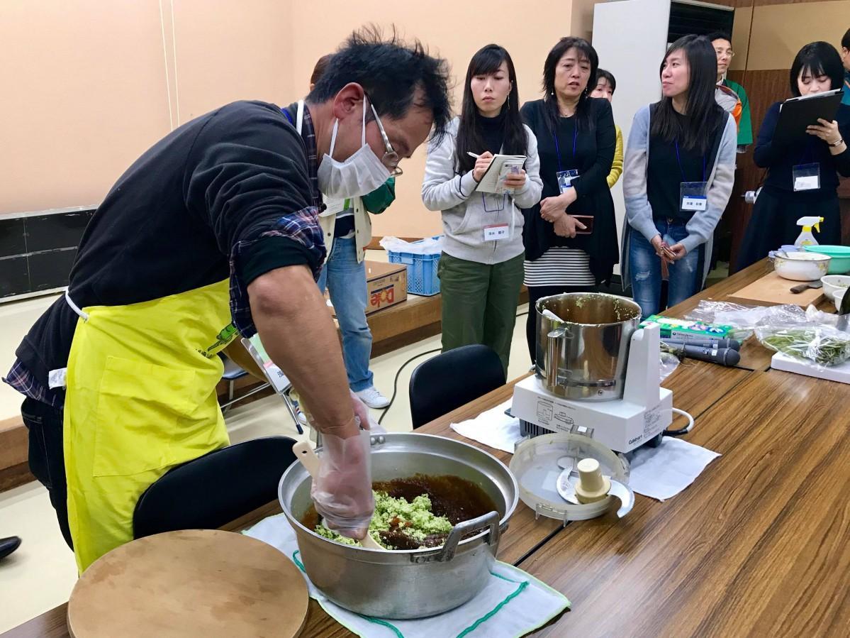 伝承会メンバーからワサビ料理を学ぶ参加者たち