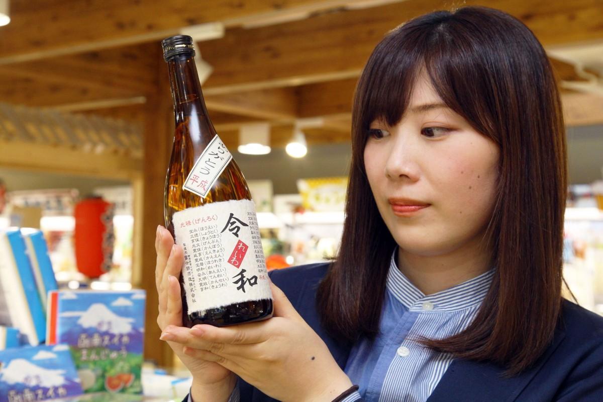 日本酒「令和」を持つ道の駅スタッフ