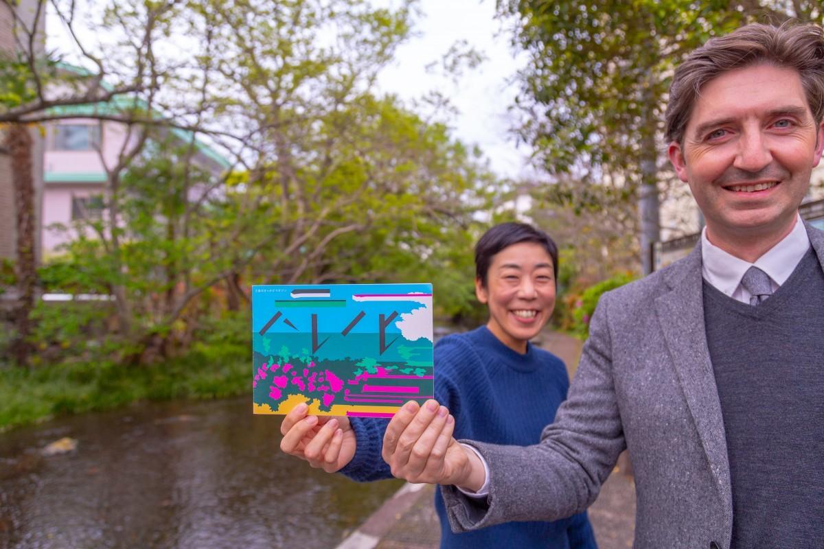 「三島で一番好きな場所」と源兵衛川で最新号を持つモロイさんと林さん