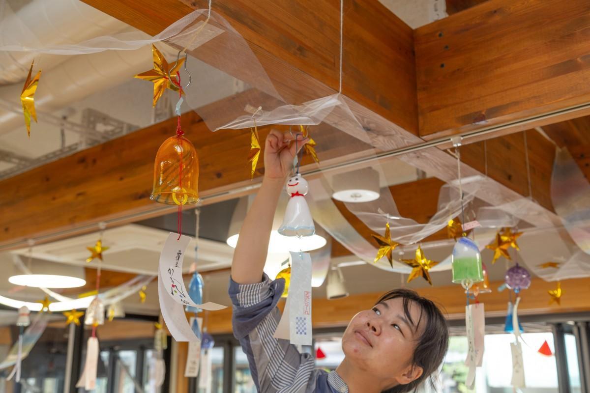 7日の雨予報を改善させるため「てるてる坊主」の風鈴を飾るスタッフ