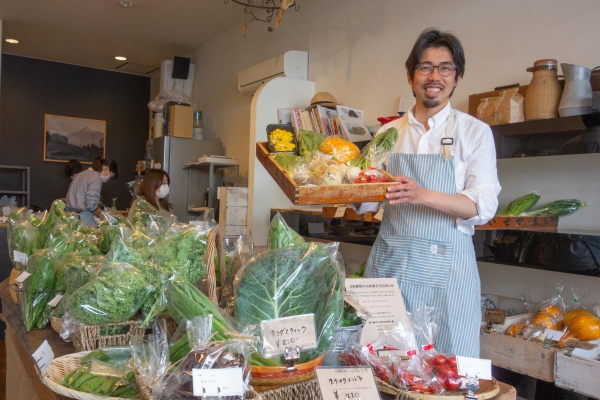 店頭で配達用の野菜を持つ小松さん