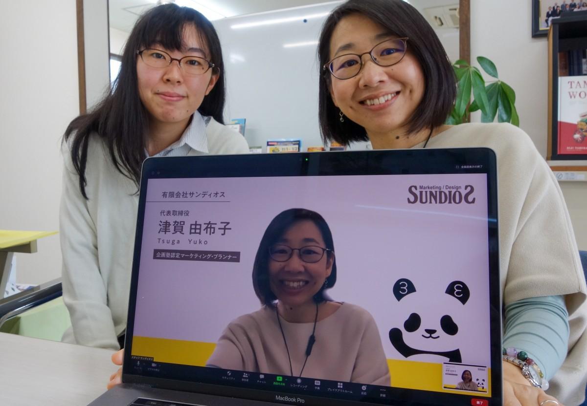 背景デザインされたモニタと、鈴木さん(左)と津賀社長