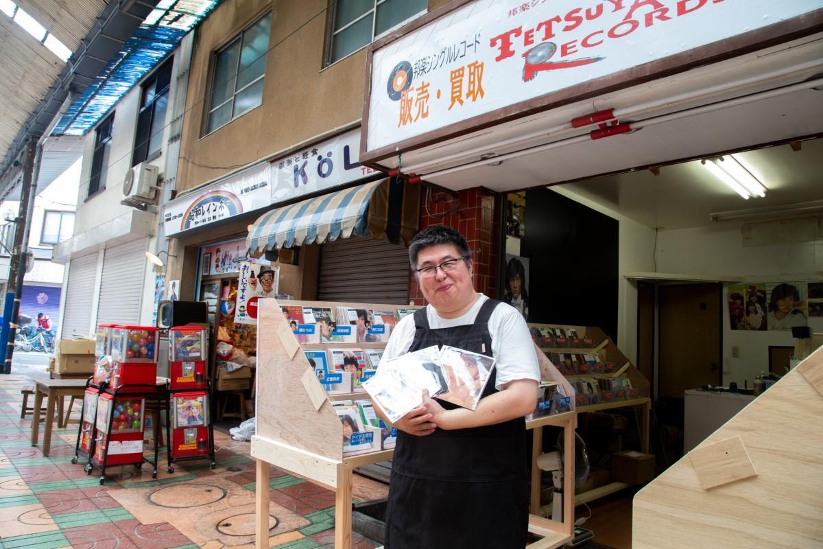 店先でお気に入りのレコードを持つ澤本さん