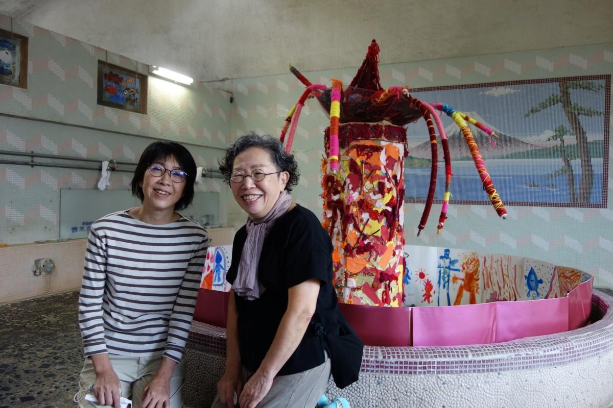 女湯のモニュメント「火の精」と兼子さん(左)と池谷さん(右)