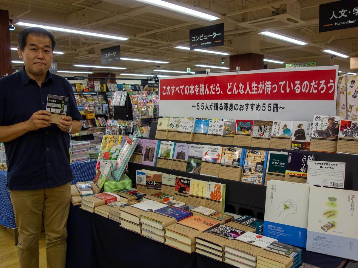 フェアの前で本を薦める長倉社長