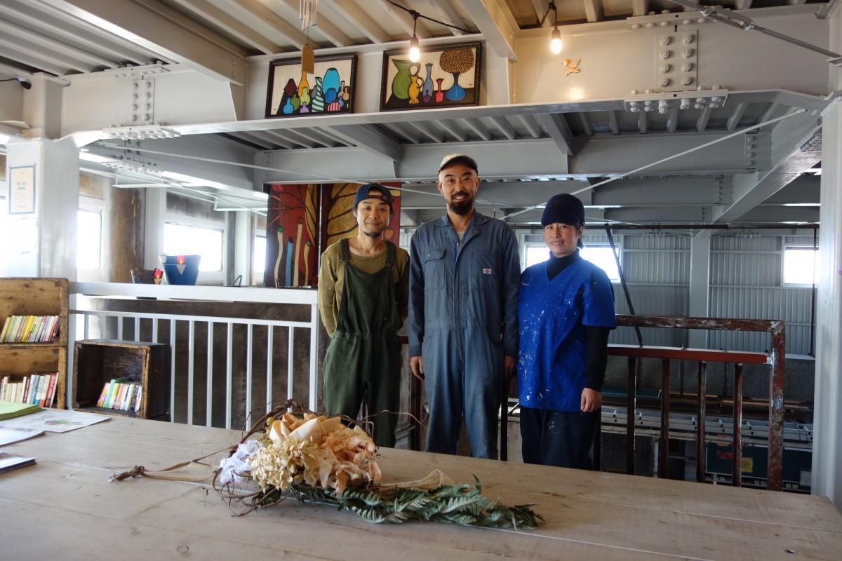 工場長の山本さん(中央)と妻の真紀さん、ボランティアスタッフの鈴木正さん