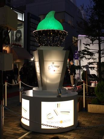 オリンピック聖火トーチがモチーフのシンボルオブジェは、炎の部分が赤、青、白、緑と色が変わる
